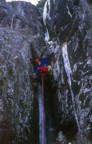 Tom climbing around the chockstone on the direct start of Left of Passage