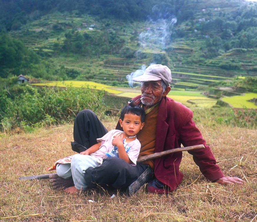 A man and his grandson take a break from working in the rice terraces