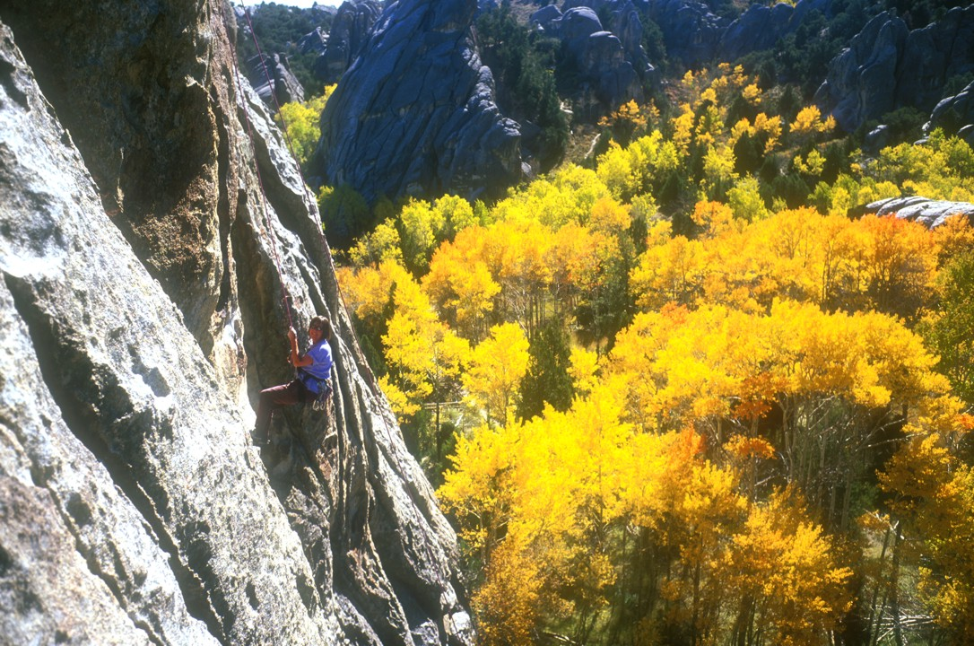 Bev lowers from the anchors with colorful fall foliage in the background