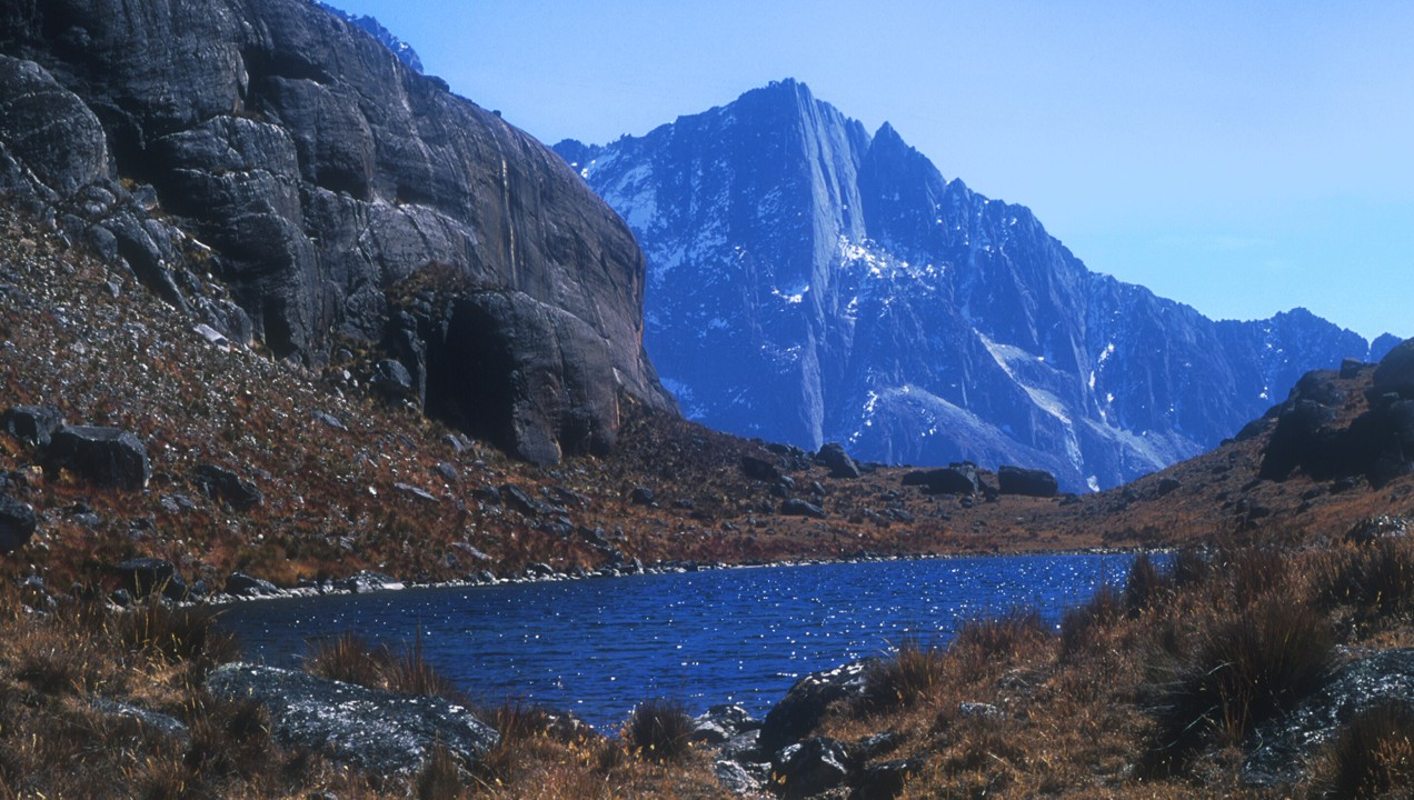 Looking east over an alpine lake at an impressive granite face