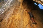 Clipping the first bolt; the route continues out the mouth of the cave at 6c