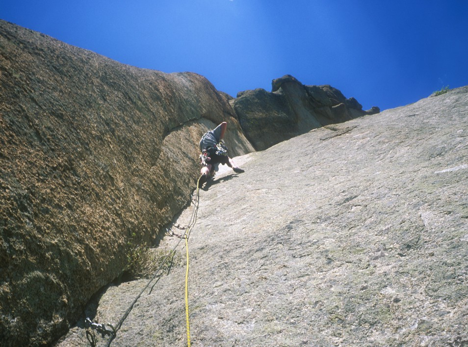 Climbing the crux bulge on the second pitch; the difficulty of this pitch is in placing gear, as it's thin and technical