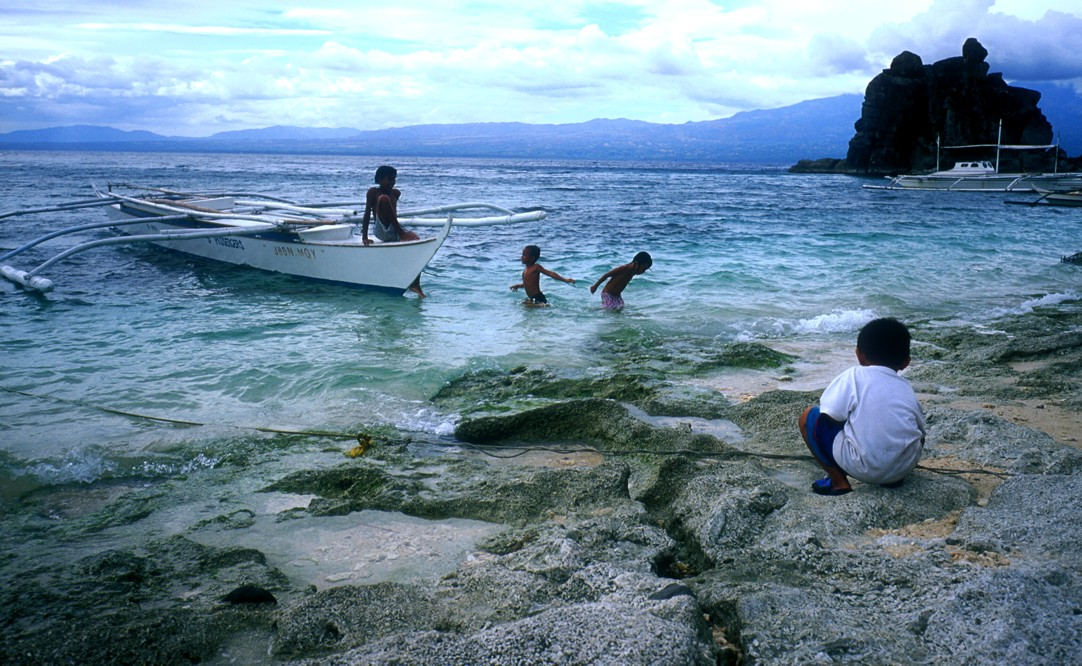 Some children playing at the beach on a small banca boat