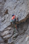Pulling though the big overhang high on the route