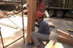 A post is positioned, making sure that the brace and horizontal member are fit at the same time