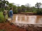Jim and the Corporal examine the fresh hippo tracks near the camp site